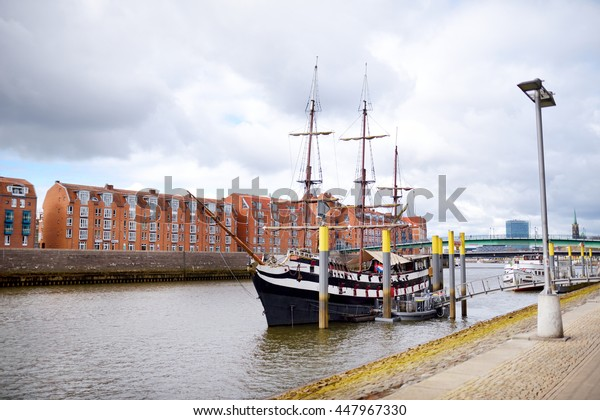 BREMEN, GERMANY - MARCH 23, 2016: A ship in front of historic facades of houses on embankment of Weser river in Bremen, Germany