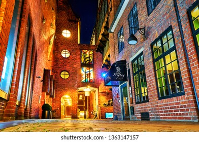 Bremen, Germany - March 31, 2019: scenic colorful night view of the famous street Böttcherstraße in frog perspective, stars can be seen in the dark sky