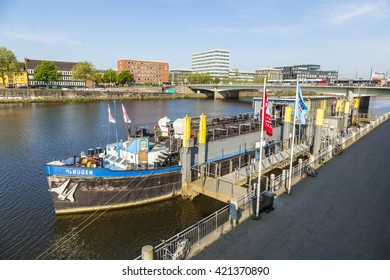 BREMEN, GERMANY - MAY 12, 2016: River Weser with ship MS Ruegen anchored at river bank. The MS Ruegen serves as theater ship nowadays organized by Knut Schakinnis.