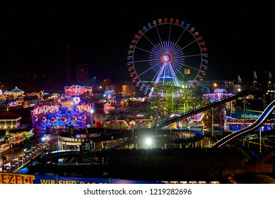 "Bremen, Germany - November 01, 2018: aerial view of the fairground ""Freimarkt"" at night while it is raining, the big giant wheel can be seen in"