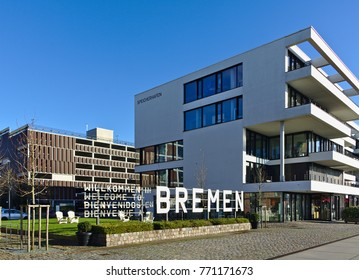 Bremen, Germany - November 25th, 2017 - Esplanade in the Überseestadt district with modern office building right next to a large metal sign saying Welcome to Bremen in German, English, Spanish, French