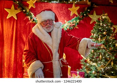 Bremen, Germany - November 30 ,2018: Man with Santa Claus traditional costume stands in front of a festive red background with stars, a decorated christmas tree and gifts, he distributes sweets