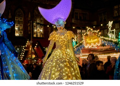 Bremen, Germany - November 30, 2018: lady on stilts dressed as the Snow Queen with beauriful white golden costume with led lights and violet head dress in shape of a lying moon at Christmas market