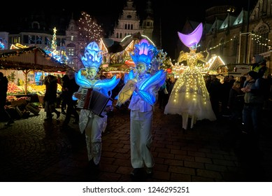 "Bremen, Germany - November 30, 2018: couple in fancy white hats and costumes  with led lights plays accordion and clarinet at the event ""Winterfantasien"" in front of stilt walkers at night"