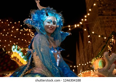 Bremen, Germany - November 30, 2018: portrait of a beautiful woman  with fancy blue costume with led lights, blue toupee and reindeer figure on top of it
