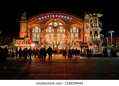 Bremen, Germany - November 30, 2018: front of the main railway station at night with beautiful christmas lights, market stalls and big traditional pyramid