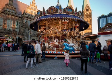 """Bremen, Germany - October 19, 2016: traditional vintage childrens' carousel in front of the town hall and St. Petri Cathedral at """"Freimarkt"""" time"""