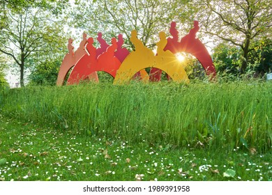 """Bremen, June 04, 2021: the colorful sculpture """"Paare"""" (pairs) by Hans-J. Müller (2002)  in a traffic roundabout in the district """"Neue Vahr Nord"""" during a beautiful sunset in spring"""