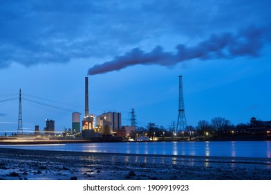 Bremen-Farge, Germany - January 26, 2021: the coal-fired power plant during scenic blue hour seen from the opposite site of the river Weser (long time exposure)