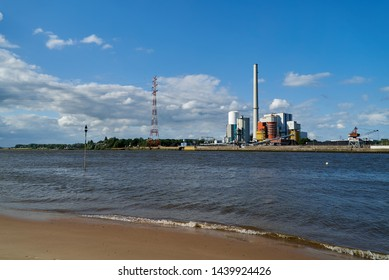 Bremen-Farge, Germany - July 01, 2019: coal-fired power station owned by US company Riverstone Holdings LLC next to the river Weser in front of vivid blue sky in summer