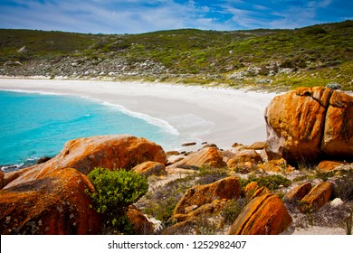Bremer Bay Western Australia. Rust colored boulders in front of a perfect white beach, turquoise ocean and lush green background of foliage.