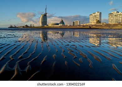 """Bremerhaven, Germany - February 03, 2019: Skyline with Atlantic Hotel Sail City, the """"Klimahaus 8° Ost"""" and """"Mediterraneo"""" seen from the mud flat at low tide with beutifully reflecting vivid blue sky"""