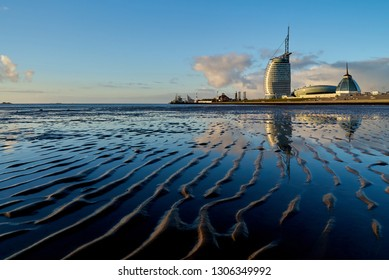 """Bremerhaven, Germany - February 03, 2019: Atlantic Hotel Sail City, the """"Klimahaus 8° Ost"""" and """"Mediterraneo"""" seen from the mud flat at low tide with beutifully reflecting vivid blue sky"""