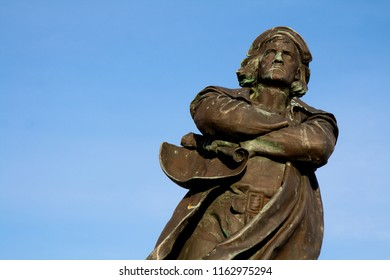 Bremerhaven, Germany - February 20, 2011: bronze sculpture of discoverer Christopher Columbus with a rolled sea map in his hands in front of blue sky