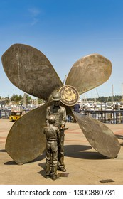 BREMERTON, WA, USA - JUNE 2018: Large metal sculpture of a ship's propeller, worker and son in Bremerton, WA. The sculpture commemorates the town's naval shipyard history.