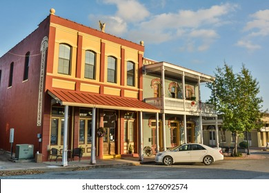 Brenham, Texas, United States of America - December 27, 2016. Exterior view of Dunlap Buildings, dating from 1870, in Brenham, TX, with commercial properties and car.