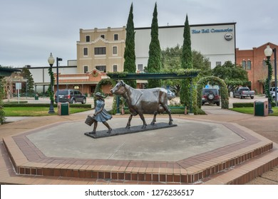 Brenham, Texas, United States of America - December 27, 2016. Exterior view of the Blue Bell Creameries factory in Brenham, TX, with monument depicting a girl with a cow.
