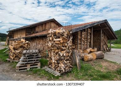 Brennholz in und vor Scheune