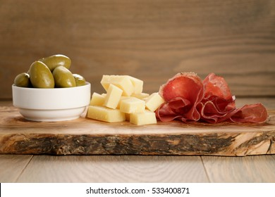 bresaola with parmesan cheese and olives on cutting board, italian antipasti