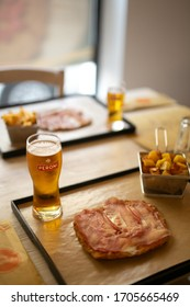 Brescia, Italy - 15 february 2020: Veal milanese (cotoletta alla milanese) with raw ham on top, with glass of beer and potatoes, italian cuisine, close-up