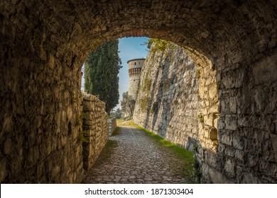 Brescia, Italy - December, 2015: Big tower in the Medieval castle of the city Brescia on a sunny clear day against a bright blue sky. Part of Brescia castle. view from the arch. Castello di Brescia