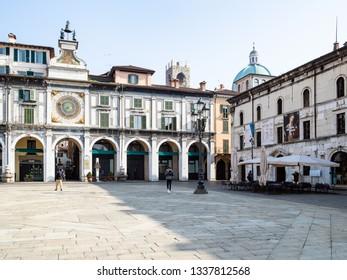 BRESCIA, ITALY - FEBRUARY 21, 2019: people on Piazza della Loggia near Clock Tower Torre dell'Orologio in Brescia city. Brescia is the second largest city in Lombardy.