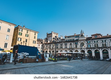 Brescia, Italy - January 13, 2018  Typical Saturday street market in Piazza Loggia (Loggia Square) around closing time. People trying to strike some last good deals as stands are closing down