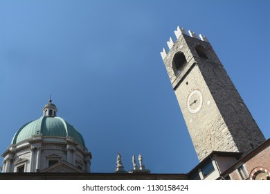 Brescia /Italy  – July 18,2017: The Broletto palace which is now the public office of the town hall of Brescia is very old and is in Romanesque architecture. Its medieval tower joins the Duomo dome.