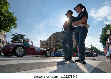 Brescia, Italy - May 19, 2018: The setting sun shines behind two Italian police officers at the finish of the Mille Miglia classic automobile rally in Brescia, Italy.