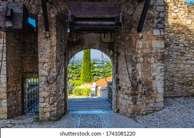 Brescia, Italy, September 11, 2019: Stone wall with merlons and drawbridge Gate of medieval Castle of Brescia or Castello di Brescia or Falcon of Italy, historical city centre, Lombardy