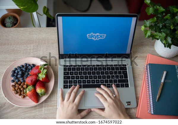 Brescia/Italy - March 2 2020: girl working remote chatting in skype with her laptop and a dish of fresh fruit