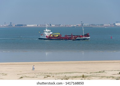 Breskens, Netherlands, 21 april 2019, couple walking on the beach from Breskens with the trailing suction hopper dredger DC Bruges in the background