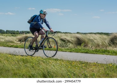 Breskens, Netherlands - June 6, 2015: A middle aged male cyclist with backpack and black and blue clothes, cycles on a bicycle path through a nature reserve near the beach on a sunny day