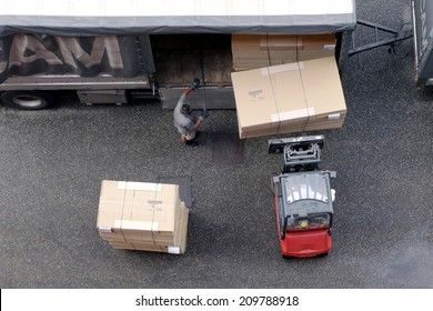 BRESSANONE, AUGUST 4, 2014: Worker loading truck on forklift. Warehouse laborer team at unloading works with forklift loader in open industrial zone in Bressanone on August 4, 2004