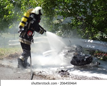 BRESSANONE, ITALY - AUGUST 1, 2013: Firefighter extinguishing the fire from the motorbike after a frontal crash collision between a car on the road. Motorbike in fire in Bressanone on August 1, 2013.