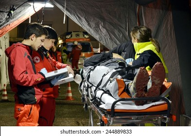 BRESSANONE, ITALY - NOVEMBER 16, 2014: Doctor checking patient on the stretcher inside a hospital field tent for the first AID. Camp room for the rescue of injured people on November 16, 2014.