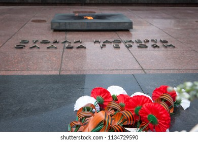 """Brest, Belarus - 05/08/2018: Flowers on the Tombstone of Unknown Soldier and Eternal Light  on Victory Day Eve. The title says """"Glory to the Heroes that fought up to the last ditch"""""""