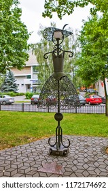 """BREST, BELARUS - JULY 12, 2018: Photo of An openwork dress on a mannequin, from the firm """"BURVIN"""". Alley of wrought lanterns. Gogol street."""