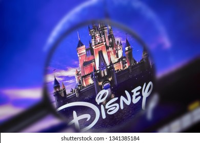 Brest, Belarus, March 15, 2019. The home page of the Disney site, view through a magnifying glass. Disney company logo is visible. Soft focus.