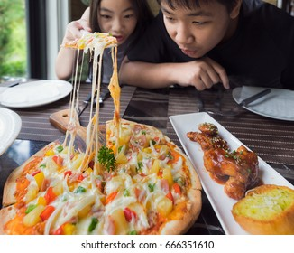 Brethren eat a pizza togather in restaurant, food, family and child concept