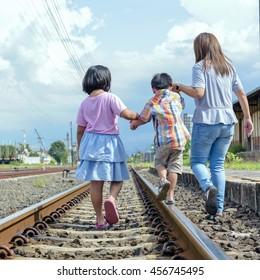 brethren hold hands walking on the railway.