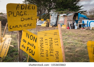 Bretignolles sur Mer, France - October 9, 2019: Set of yellow sign on a protest zone in an area to defend ZAD (Acronym of Zone to Defend) against the construction of the boat harbor