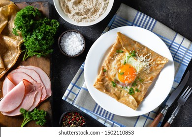 Breton crepe, Savory Buckwheat Galettes Bretonnes with fried egg, cheese, ham on a white plate on a kitchen table with ingredients on a cutting board, view from above, flatlay