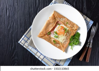 Breton crepe, Savory Buckwheat Galettes Bretonnes with fried egg, cheese, ham served on a white plate on a wooden table, french cuisine, view from above, flatlay, free space