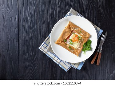 Breton crepe, Savory Buckwheat Galettes Bretonnes with fried egg, cheese, ham served on a white plate on a black wooden table, french cuisine, view from above, flatlay, free space