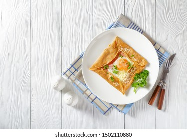 Breton crepe, Savory Buckwheat Galettes Bretonnes with fried egg, cheese, ham served on a white plate on a wooden table, view from above, flatlay, free space for text