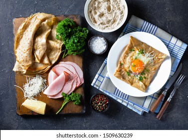 Breton crepe, Savory Buckwheat Galettes Bretonnes with sunny side up egg, cheese, ham on a white plate on a kitchen table with ingredients on a cutting board, view from above, flatlay