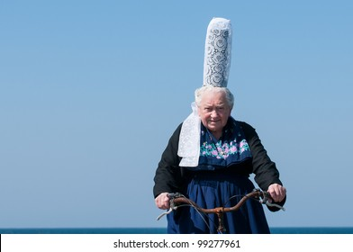 breton women headdress under a blue sky with bicycle