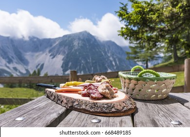 Brettljause on wooden table on Klagenfurter Huette with view to mountain Weinasch in Karawanks