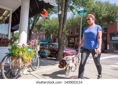 BREVARD, NC (USA) - July 7, 2019:  A woman walks her dog at the downtown intersection of Broad and Main Streets on an early Sunday morning.